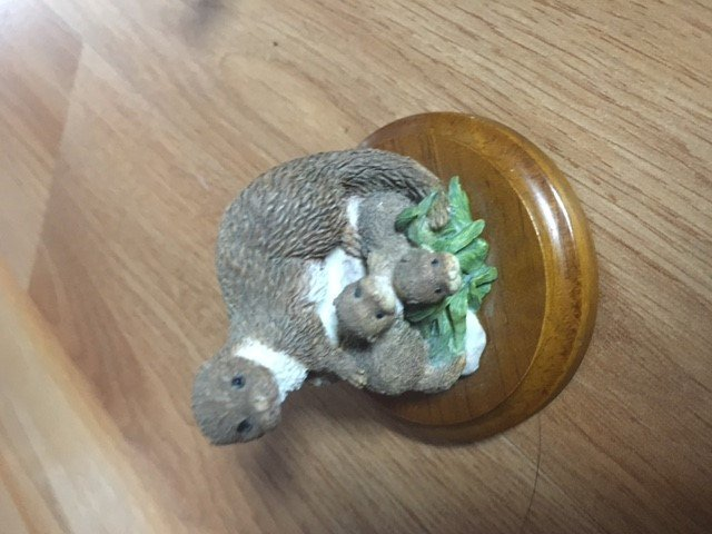 115. Ferret figurine on wood